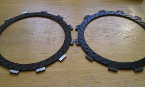 On the left, a new friction plate. On the right, the old, worn friction plate.